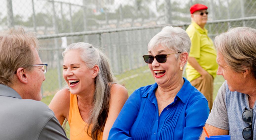 Tres hombres y dos mujeres mayores de 65 disfrutando de una conversación en un parque